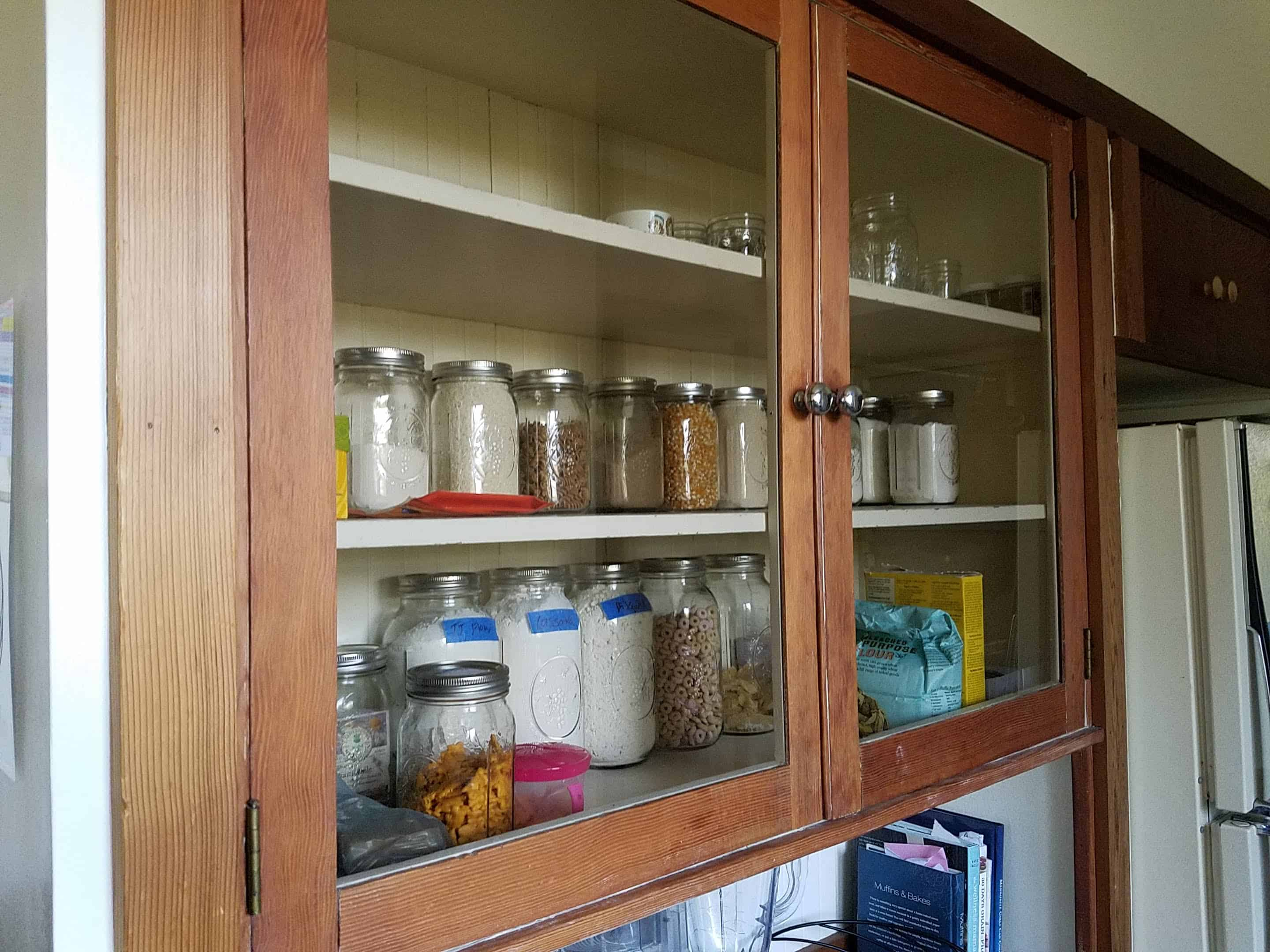 minimalist kitchen cabinet with dry goods in mason jars