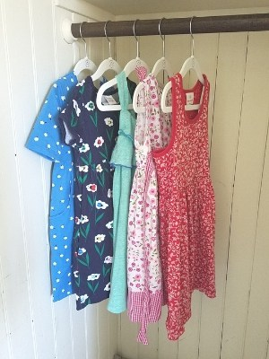 five dresses hanging in minimalist kids closet
